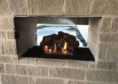 rock fire pit by the backyard pool