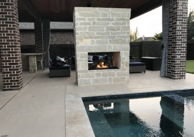 backyard pool design with rock fire pit